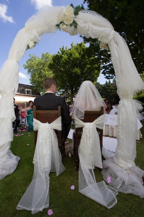 Heel romantisch achter het bruidspaar tijdens een ceremonie in een tuin