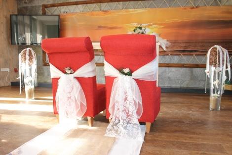 Stoelversiering met bruidsstof en bloemen.