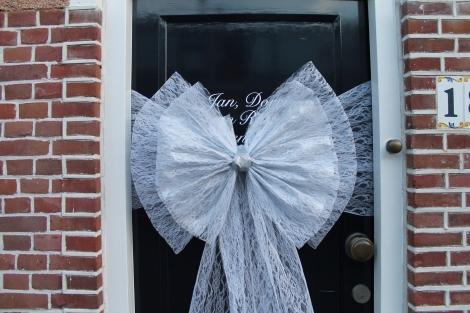 Kerststrik in witte kant met zilver. Band om de deur in witte kant. Kosten € 30,--